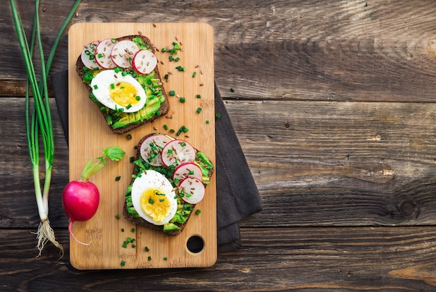 Toasts à l'avocat, œufs, radis, oignon vert et graines de lin sur fond de bois rustique. vue de dessus. copiez la zone d'espace.