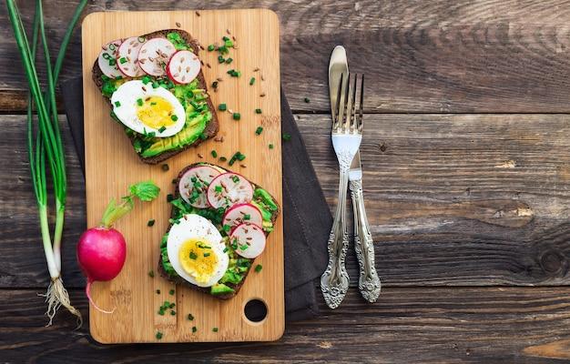 Toasts à l'avocat, œufs, radis, oignon vert et graines de lin sur fond de bois rustique. vue de dessus.