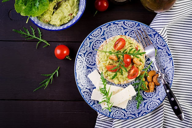 Toasts d'avocat sains pour le petit déjeuner, guacamole, olives kalamata, tomates, noix de cajou et fromage feta