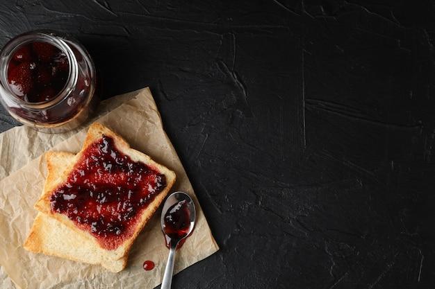 Toasts et bocal en verre avec de la confiture, une cuillère et du papier sulfurisé sur fond noir, copiez l'espace