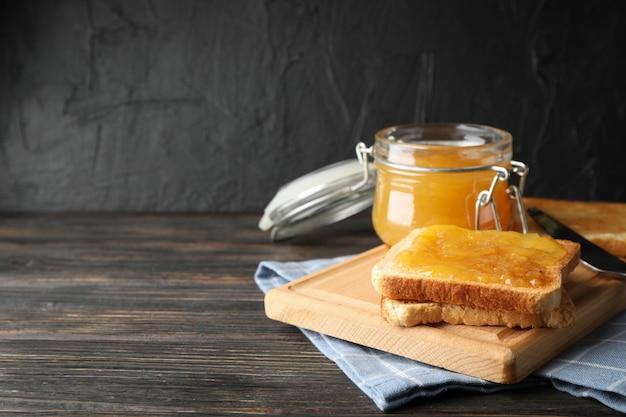 Toasts avec confiture d'abricot, planche, serviette et pot sur fond en bois, espace pour le texte
