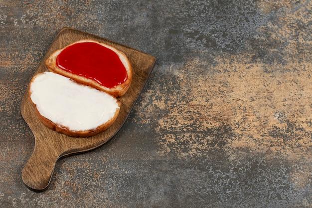 Toasts avec de la confiture et de la crème sure sur planche de bois.