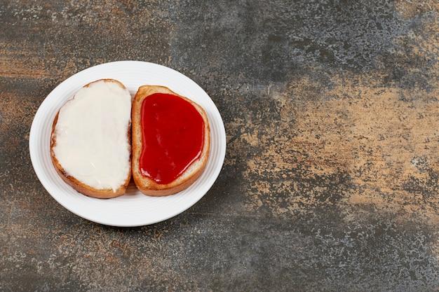 Toasts avec confiture de fraises et crème sure sur plaque blanche.