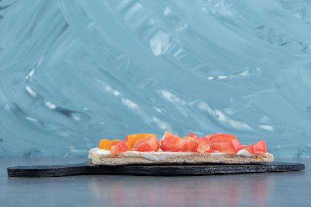 Toasts croustillants aux tomates sur planche de bois.