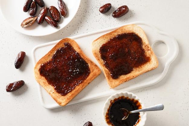 Toasts croustillants frais avec de la confiture de dattes sans sucre sur tableau blanc