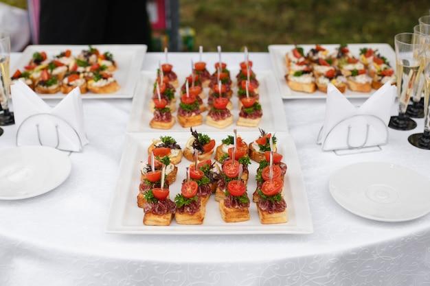 Toasts délicieux servis sur des assiettes blanches à la réception de mariage.