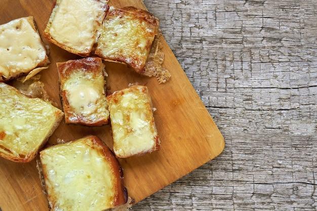 Toasts fraîchement cuits au four avec du fromage fondu sur une planche à découper sur des planches en bois