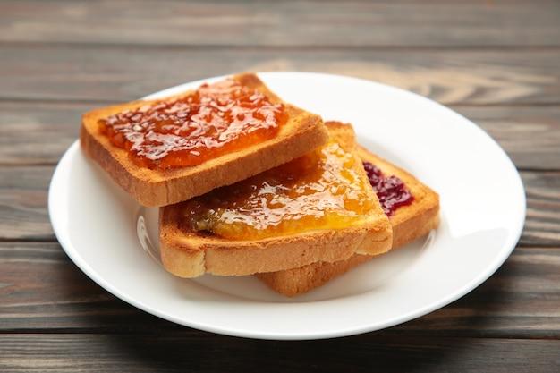Toasts frais avec du beurre et différentes confitures sur table. vue de dessus