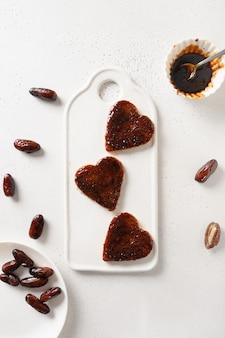 Toasts frais en forme de coeur avec de la confiture de dattes sans sucre pour un délicieux petit déjeuner sur tableau blanc