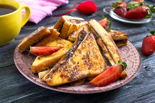 Toasts français sucrés avec banane, chocolat, fraises sur une surface en bois. petit déjeuner savoureux