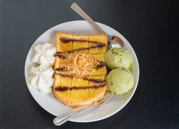 Toasts de miel avec dessert glacé au thé vert au fond de plaque blanche ondark.