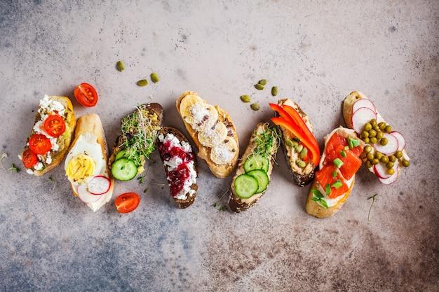 Toasts ouverts avec différentes garnitures sur fond gris-brun, espace de copie, vue de dessus