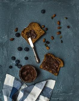 Toasts de pain de grains entiers avec beurre d'arachide au chocolat végétalien biologique, myrtille, noix sur un tableau gris grunge