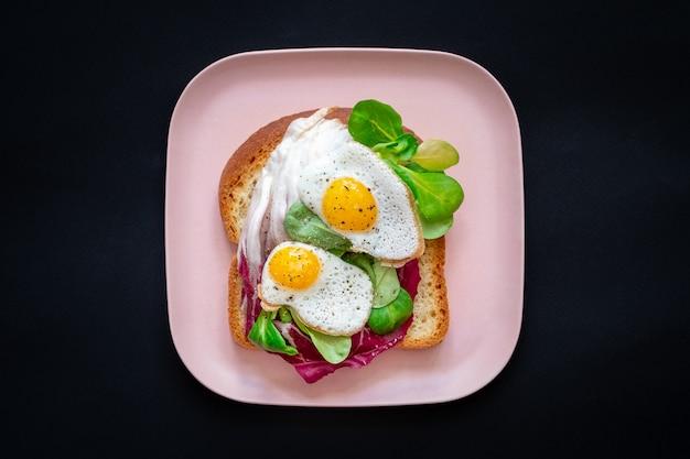 Toasts de pain avec œufs au plat et salade verte