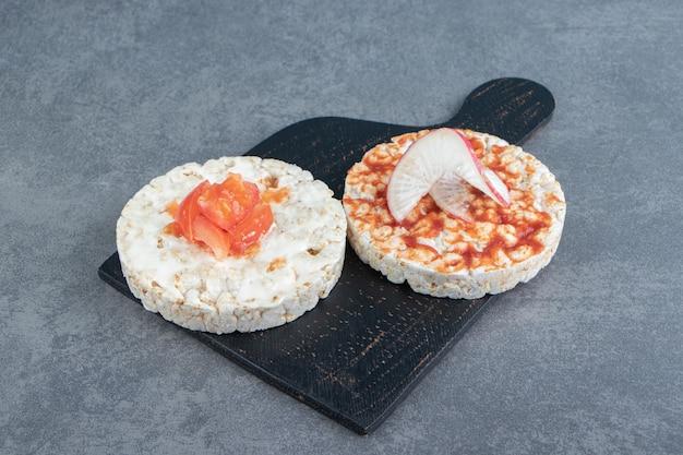 Toasts de riz soufflé croustillant aux tomates sur planche de bois.