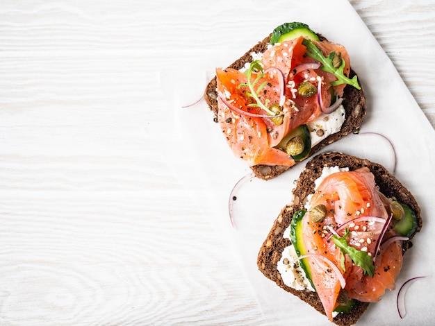 Toasts sains avec pain de seigle avec fromage à la crème, saumon, concombre frais, câpres, graines de sésame, poivre noir et roquette sur papier blanc. espace copie