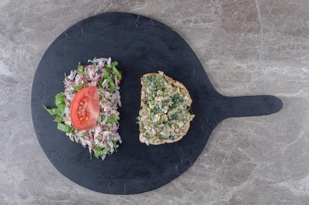 Toasts avec salade savoureuse sur tableau noir.