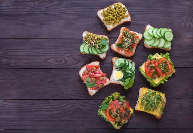 Toasts, sandwichs au fromage à la crème, concombres, tomates, saumon, pousses, oeuf sur un bois brun ¡