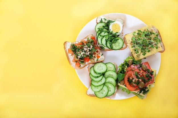 Toasts, sandwichs aux concombres, tomates, œufs, pousses, herbes et noix sur une assiette sur un jaune