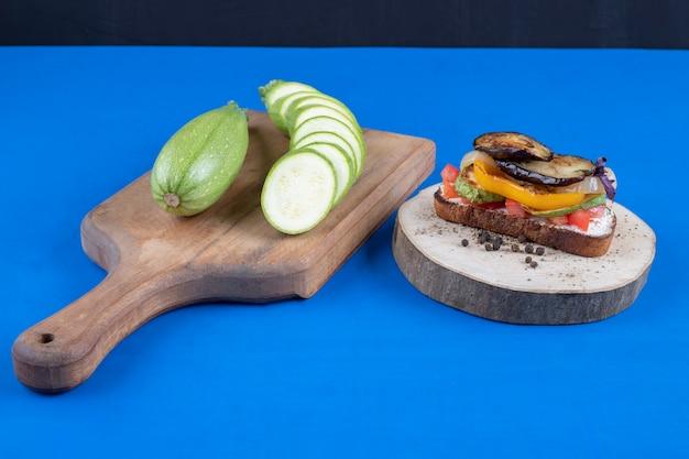 Toasts savoureux avec des légumes sur un morceau de bois avec des courgettes tranchées