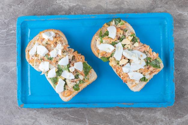 Toasts savoureux avec des légumes tranchés sur plaque bleue.