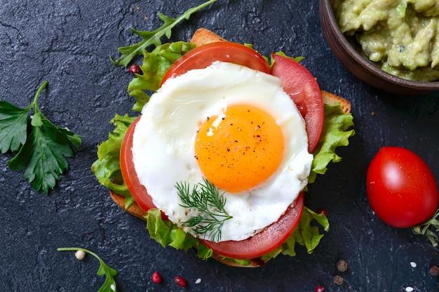 Toasts de seigle avec purée d'avocat, œuf au plat, tomate fraîche, herbes. petit déjeuner savoureux. nutrition adéquat. sandwich à l'oeuf.
