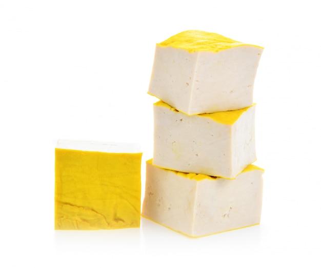 Tofu jaune sur une surface blanche