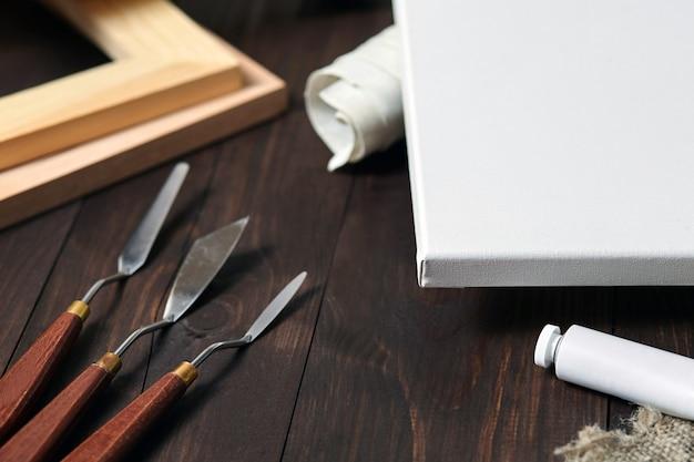 Toile avec des couteaux à palette près des barres de civière en bois et un tube avec de la peinture à l'huile