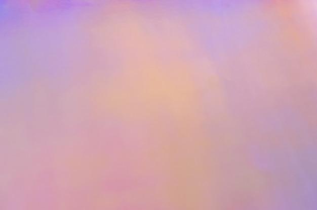 Toile de fond de couleurs pastel doux abstrait holographique. gros plan de papier d'aluminium holographique. fond coloré tendance moderne.