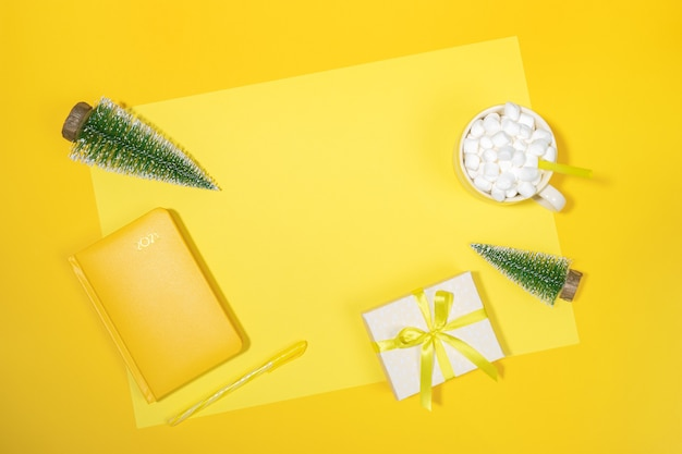Toile de fond de l'espace de travail de noël. bloc-notes jaune - organisateur sur 2021, petits arbres de noël, tasse de café avec des guimauves, coffret cadeau bricolage sur jaune. en résumé, planification. vue de dessus, mise à plat, espace de copie.
