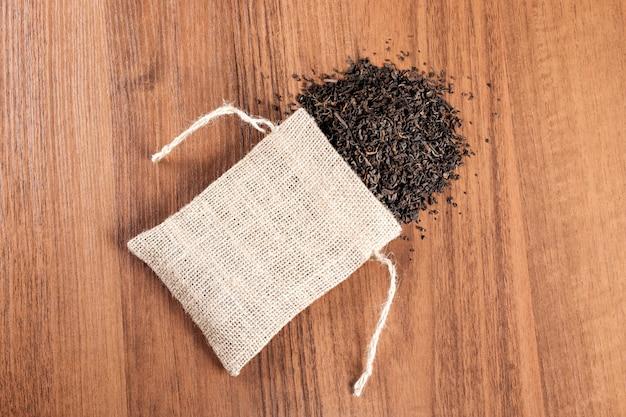 Toile de jute vintage avec du thé sur la table en bois