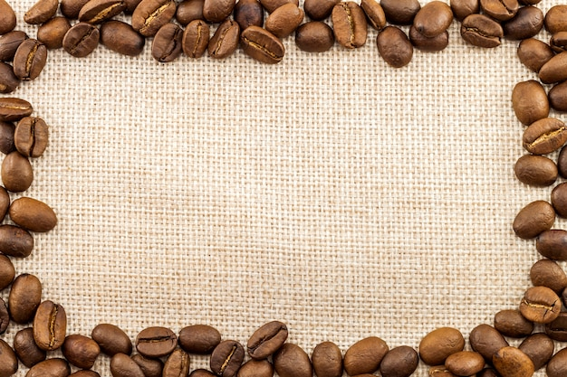 Toile de sac en toile de jute et grains de café placés en rond dans le fond de photo de cercle. copiez l'espace. frontière de café