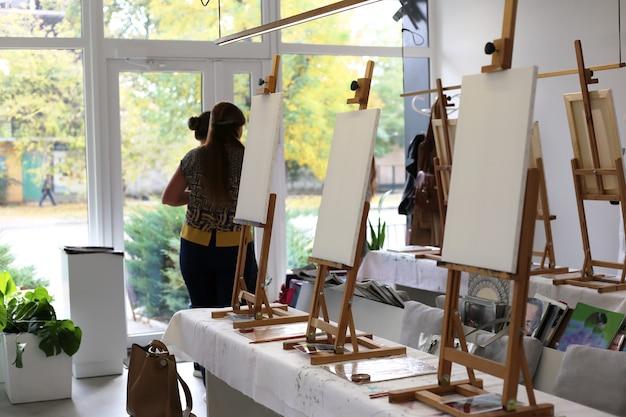 Des toiles avec des châssis se tiennent sur des chevalets dans un atelier d'art leçon de peinture