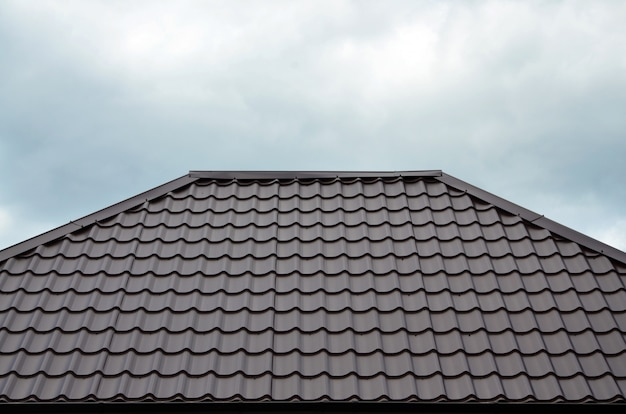 Toiles de toit marron ou bardeaux sur la maison comme image de fond. nouveau motif de texture de matériau de toiture de style classique marron chevauchant sur une maison réelle