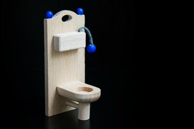 Toilette jouet en bois sur fond noir