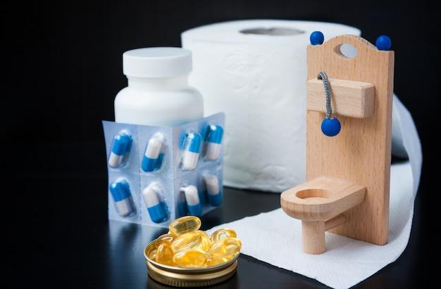 Toilette jouet en bois, pilules et réveil sur fond noir
