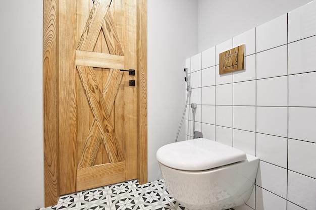 Toilette ou wc moderne à chasse d'eau dans petite salle de bain avec bouton poussoir. personne