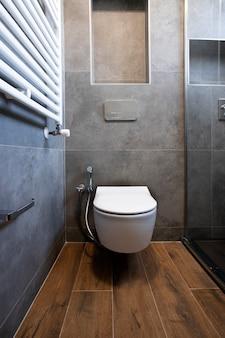 Toilettes flottantes dans une salle de bains design avec mur en pierre grise et parquet