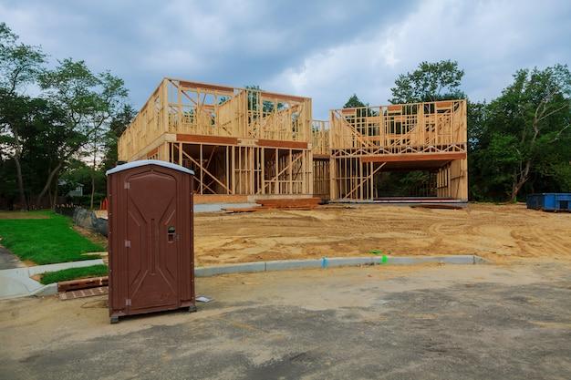 Toilettes mobiles sur une nouvelle structure près de la nouvelle maison en construction.