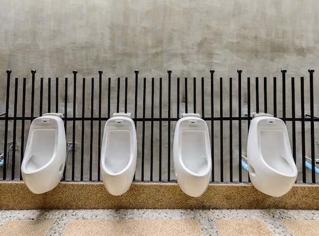 Toilettes publiques - urinoir avec toilettes confort pour hommes, urinoirs blancs dans des toilettes publiques