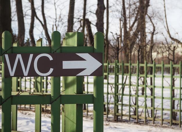 Toilettes wc signe sur une clôture verte dans un lieu public.