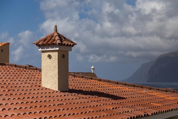 Toit en bardeaux orange avec cheminée. ciel nuageux et montagnes. los gigantes, île de tenerife.