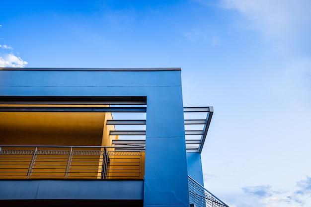 Le toit d'un bâtiment design droit peint en bleu derrière un ciel clair et clair
