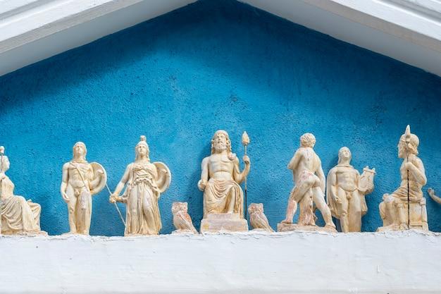 Toit d'un bâtiment fait dans le style de la grèce antique avec de petites statues dessus, grèce