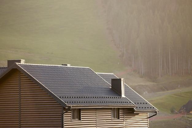 Toit de chalet avec murs de parement, toit en bardeaux bruns et hautes cheminées dans une zone écologique sur un paysage brumeux le jour d'été ensoleillé.