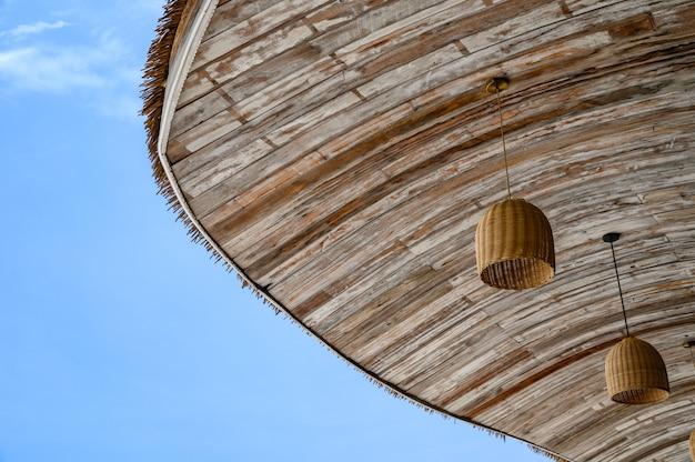 Toit de chaume en bois avec lampe suspendue et ciel