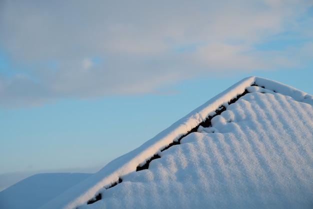 Toit couvert de neige contre le fond d'hiver de ciel bleu en ecosse