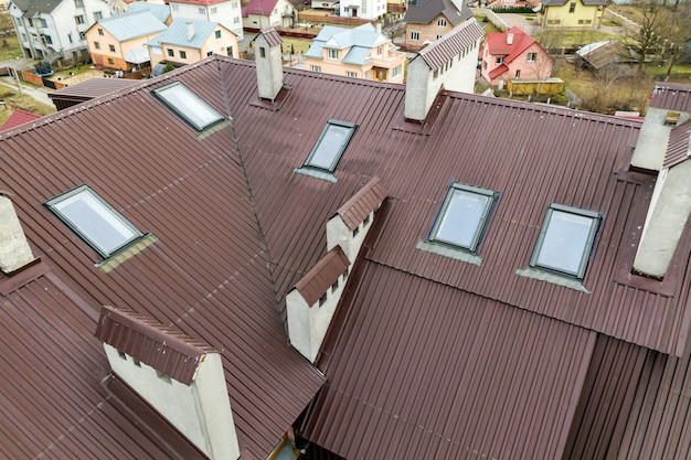 Toit d'une maison en tôle avec fenêtres mansardées.