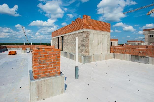 Le toit d'une nouvelle maison en construction avec un mur de briques d'une maison monolithique