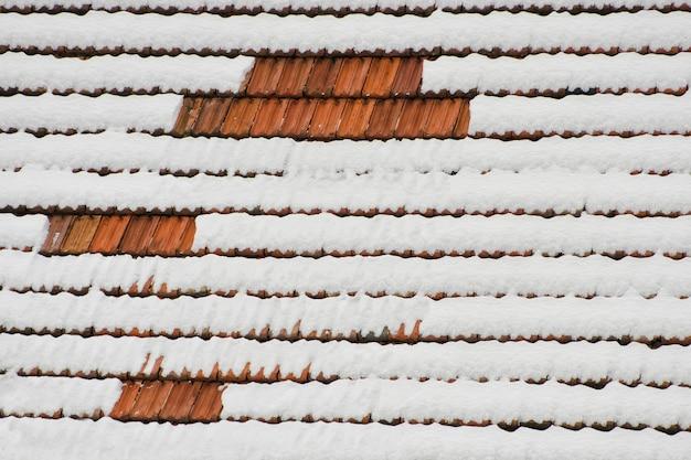Le toit de tuiles d'argile recouvert de neige. texture